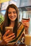 Młoda kobieta używa mądrze telefon i kredytową kartę Zdjęcie Royalty Free