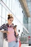 Młoda kobieta używa mądrze telefon na zewnątrz budynku biurowego zdjęcie royalty free