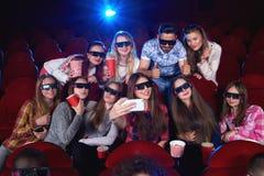 Młoda kobieta używa mądrze telefon przy kinem Obrazy Stock