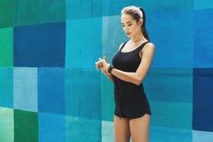 Młoda kobieta używa mądrze zegarek, jaskrawy backgroud obrazy stock