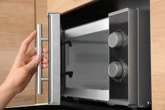 Młoda kobieta używa mikrofala piekarnika w kuchni obrazy royalty free