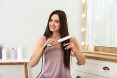 Młoda kobieta używa nowożytnego włosy żelazo zdjęcie stock