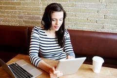 Młoda kobieta używa pastylkę Fotografia Stock