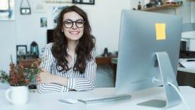 Młoda kobieta używa pastylka komputer przy biurem lub szkołą patrzeje kamerę zbiory