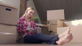 Młoda kobieta używa pastylka komputer przy jej nowym domem podczas gdy siedzący na podłoga zdjęcie wideo