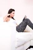 Młoda kobieta używa pastylka peceta na kanapie fotografia royalty free