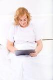 Młoda kobieta używa pastylka peceta w łóżku zdjęcia stock