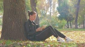 Młoda kobieta używa pastylki plenerowego obsiadanie na trawie Dziewczyna używa cyfrowego pastylka komputer osobistego w jesień pa zdjęcie wideo