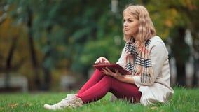 Młoda kobieta używa pastylki plenerowego obsiadanie na trawie i ono uśmiecha się zbiory