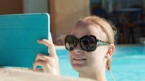 Młoda kobieta używa pastylki poolside zdjęcie wideo