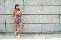 Młoda kobieta używa pastylki pozycję przeciw ścianie w mieście Obrazy Stock