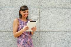Młoda kobieta używa pastylki pozycję przeciw ścianie w mieście Obraz Royalty Free