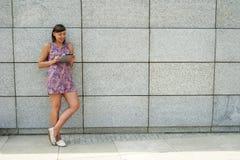 Młoda kobieta używa pastylki pozycję przeciw ścianie w mieście s Zdjęcia Royalty Free