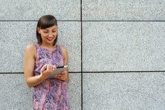 Młoda kobieta używa pastylki pozycję przeciw ścianie w mieście s Zdjęcia Stock