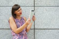 Młoda kobieta używa pastylki pozycję przeciw ścianie w mieście s Zdjęcie Stock