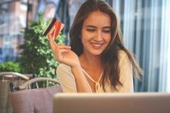 Młoda kobieta używa podołek odgórną i kredytową kartę obrazy royalty free