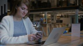 Młoda kobieta używa smartphone w kawiarni, pisać na maszynie sms zdjęcie wideo