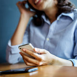 Młoda kobieta używa smartphone z bezprzewodowym hełmofonem zdjęcia royalty free