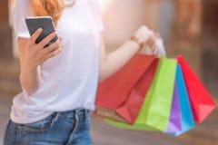 Młoda kobieta używa smartphone z torba na zakupy w innej ręce Zdjęcia Stock