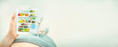 Młoda kobieta używa sprawność fizyczną app na jej smartphone po treningu fotografia stock