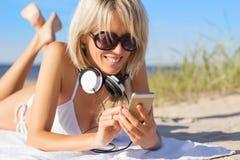 Młoda kobieta używa telefon komórkowego i będący ubranym hełmofon Zdjęcia Royalty Free