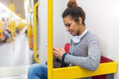 Młoda kobieta używa telefon komórkowego na metrze Fotografia Stock