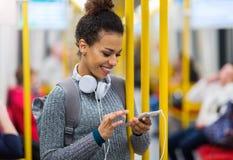 Młoda kobieta używa telefon komórkowego na metrze Zdjęcie Stock