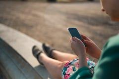 Młoda kobieta używa telefon w pałac parka obsiadaniu na fontannie - Zamyka w górę obraz royalty free