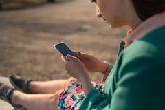 Młoda kobieta używa telefon w pałac parka obsiadaniu na fontannie - Zamyka w górę zdjęcia stock