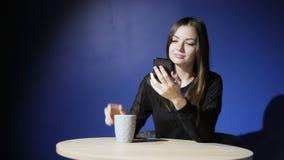 Młoda kobieta używa telefonu i napoju kawę w kawiarni Używać smartphone, wyszukujący, czytający, gawędzący zbiory