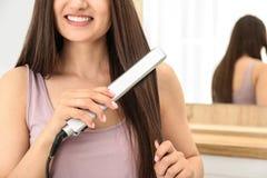 Młoda kobieta używa włosy żelazo indoors Przestrze? dla teksta fotografia stock