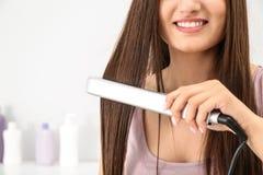 Młoda kobieta używa włosy żelazo indoors, zbliżenie zdjęcie royalty free