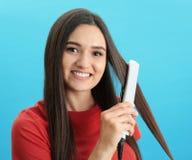 Młoda kobieta używa włosy żelazo na błękitnym tle obrazy royalty free