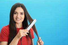 Młoda kobieta używa włosy żelazo na błękitnym tle obraz stock