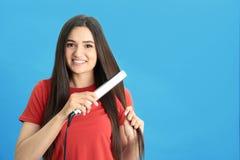 Młoda kobieta używa włosy żelazo na błękitnym tle obrazy stock