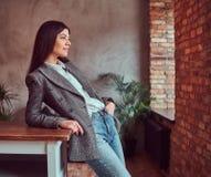 Młoda kobieta ubierał w szarej eleganckiej kurtce pozuje podczas gdy opierający na stole w pokoju z loft wnętrzem, patrzeje dalek obraz stock