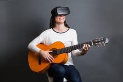 Młoda kobieta uczenie dlaczego bawić się gitarę przez wirtualnego reala Fotografia Royalty Free