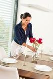 Młoda kobieta umieszcza kwiatu obiadowego stół Zdjęcie Stock