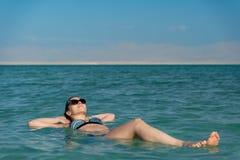 Młoda kobieta unosi się na wodnej powierzchni nieżywy morze zdjęcie royalty free