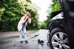 Młoda kobieta uszkadzającym samochodem po wypadku samochodowego, robi rozmowie telefonicza Zdjęcie Royalty Free