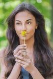 Młoda kobieta wącha żółtego kwiatu Obrazy Stock