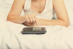 Młoda kobieta w łóżku z kalkulatorem Rodzinny budżet Kredyt, Zdjęcia Stock