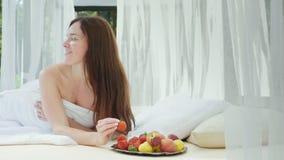 Młoda kobieta w łóżku z truskawką w jej ręce Kłamstwa basenem na lounger z zasłonami Romansowy miesiąc miodowy zbiory