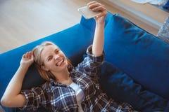 Młoda kobieta w żywym izbowym lying on the beach na trenerze bierze selfie obrazki w domu obraz stock