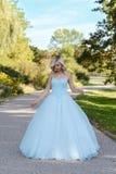 Młoda kobieta w błękitnej balowej todze w ogródzie Zdjęcie Stock