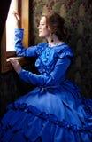 Młoda kobieta w błękitnej rocznik sukni przyglądającej out okno w wyczynie Zdjęcie Stock
