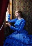 Młoda kobieta w błękitnej rocznik sukni przyglądającej out okno w wyczynie Obrazy Stock