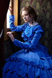Młoda kobieta w błękitnym rocznik sukni obsiadaniu w coupe blisko wygrany obraz royalty free