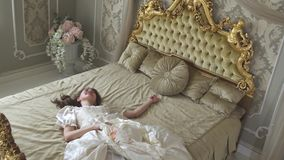 Młoda kobieta w balowej todze spada na złoto dekorującym łóżkowego mienia jedwabniczym kapeluszu Dziewczyna jest zmęczona i śpiąc zbiory wideo