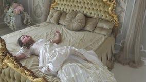 Młoda kobieta w balowej todze spada na złoto dekorującym łóżku zamkniętym w górę Dziewczyna jest zmęczona i śpiąca Kobieta odpocz zbiory wideo
